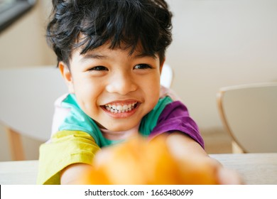 Little boy hold the sausage croissant in his hands with smile of happiness on his face.