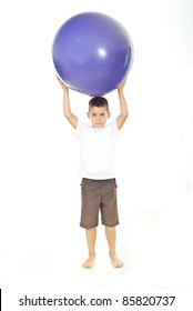 Little boy holding big pilates ball on his head isolated on white background