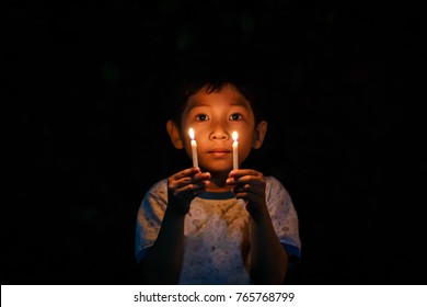Little boy holding candle blur