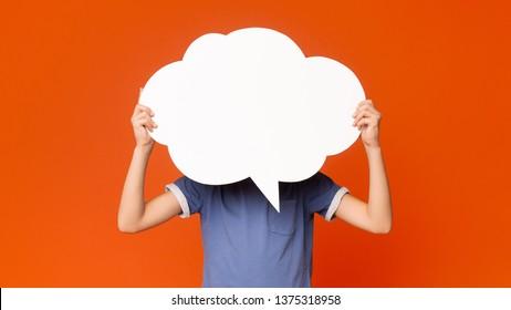 Little boy holding an empty speech bubble in front of his head, orange studio background, free space