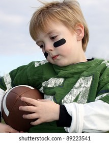 Little boy holding a football, American