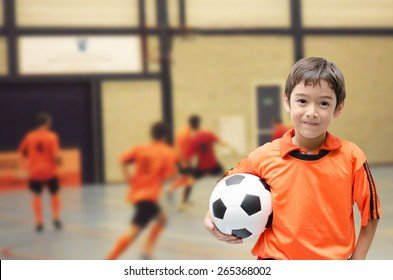 Little boy holding football soccer ball indoor gym