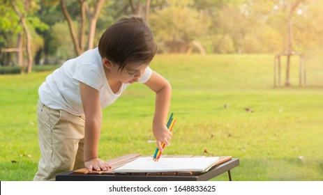 Little boy holding four colorpencils, red, blue, green and yellow drawing on white paper in the park.