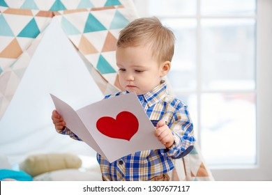 Little boy holding gift card with red heart. Family holiday, mother's day.