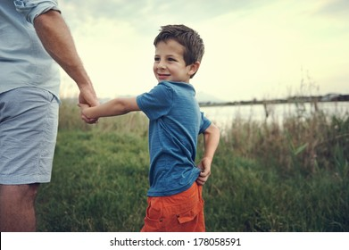 little boy holding hands with dad and smiling over his shoulder