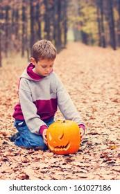 Little boy holding his Halloween pumpkin