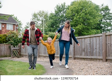 Little boy holding his parents hands as they walk along the garden path to get back to the house. They are smiling and laughing on the way back.