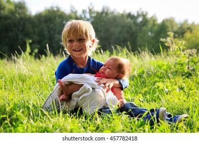 little boy holding newborn sister in summer nature