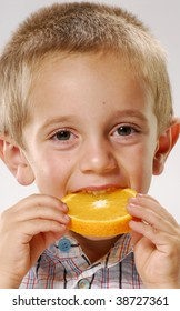 Little boy holding an orange wheel. Little boy eating orange.