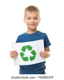 Little boy holding paper sheet with recycling symbol on white background