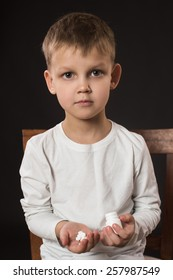 Little boy holding pills in his hands