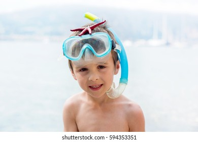 Little boy holding red five point starfishes in his hands on the sandy beach