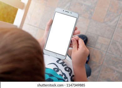 Little boy holding smartphone in vertical position with empty white screen. Kid play game, surfing online, learning...etc. Mockup