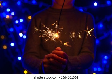 A little boy is holding a sparkler fire on the background of a Christmas tree. New Year 2020