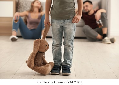 Little boy holding toy bunny while his parents drinking alcohol on background