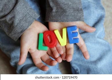 Little boy holding the word love made from childrens letter magnets