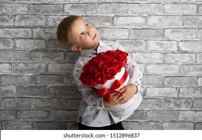 A little boy holds a big red box with red and white roses.