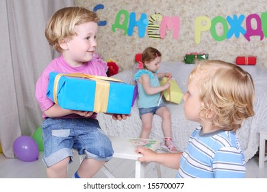 Little boy holds blue box with gift and other boy lokks et he and girl sits with gift at sofa at funny children party. Focus on boys. Inscription Happy Birthday on wall.