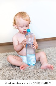The little boy holds a bottle of water