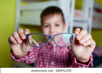 Little boy holds in his hands the glasses. Kid has poor vision. Child examines your eyes ophthalmologist.