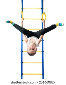 Little boy holds on sports rings and hanging upside down on a white background