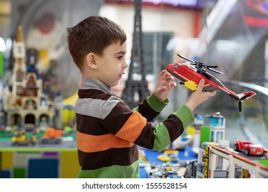 a little boy holds a toy helicopter in kindergarten