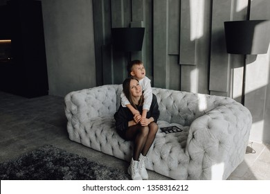 Little Boy Hug his Beautiful Mother Long Shot. Young Woman in Black Dress and Happy Blond Son Wearing White Shirt Sitting on Gray Couch, Hugging. Caucasian Smiling Family at Modern Living Room