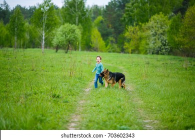 Little boy with a huge dog stands in the middle of a dirt road on a green meadow