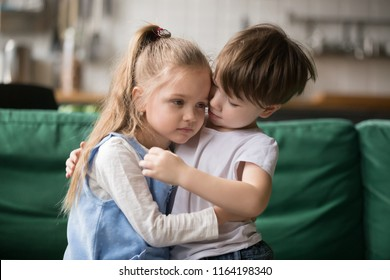 Little boy hugging consoling upset girl sitting on sofa, kid brother embracing sad sister apologizing or comforting, siblings friendship, preschool children good relationships and support concept