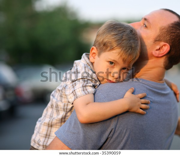 Little boy hugging hugging father around shoulders
