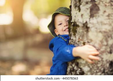 Little boy hugging a tree