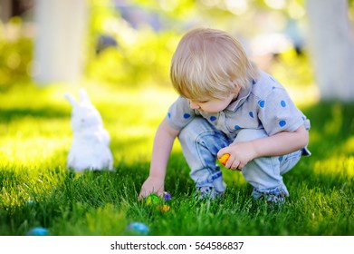 Little boy hunting for easter egg in spring garden on Easter day. Cute little child with traditional bunny celebrating feast