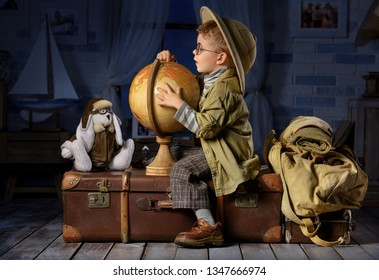 Little boy in the image of a tourist playing with a globe in his room