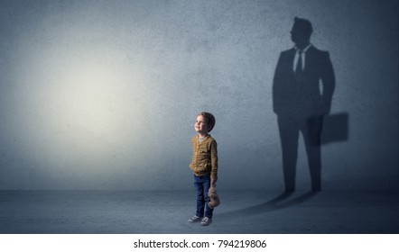 Little boy imagine that he will be businessman and illustrating his future in a big shadow