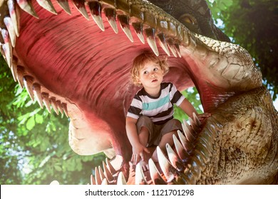 Little boy inside of a dinosaur's mouth in dino park