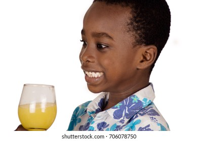 Little boy isolated on white background is happy to drink fruit juice in the glass he holds.