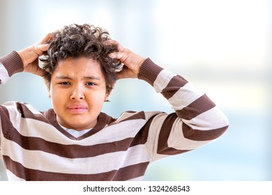 Little boy itchy his hair on white background