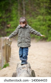 Little boy in jacket walking on wood at park