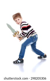 little boy in jeans and a striped shirt waving a plastic sword-isolated on white background
