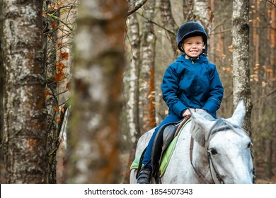 Little boy in a jockey cap on a white adult horse on a background of nature. Jockey, hippodrome, horseback riding.