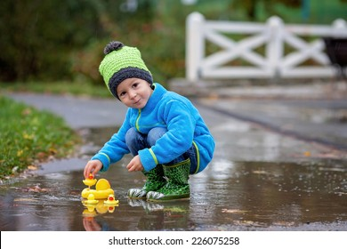 Little boy, jumping in muddy puddles in the park, rubber ducks in the puddle
