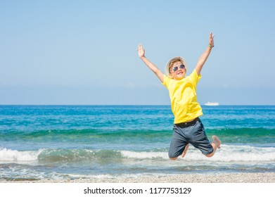 Little boy jumping on the beach. Travel concept. Space for text.