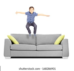 Little boy jumping on a sofa isolated on white background