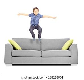 Petit garçon sautant sur un canapé isolé sur fond blanc