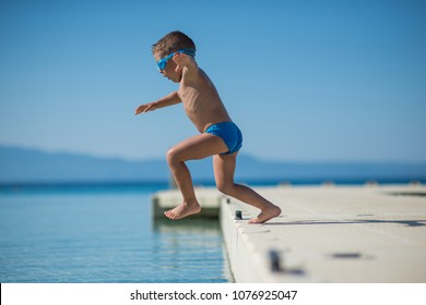 Little boy jumping from wooden pier into sea water