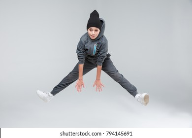 A little boy jumps up with his legs spread wide. On a gray background.