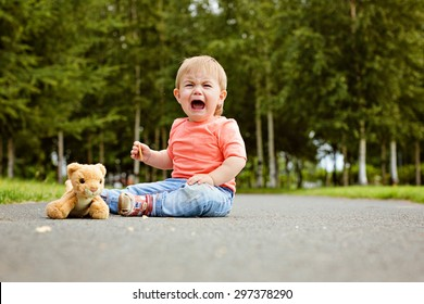 Little boy the kid in blue jeans crying bitterly, sitting on the ground next to a soft toy in the summer