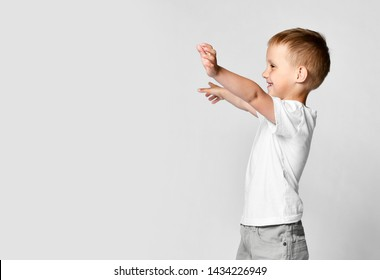 Little boy kid shows hugs with open arms side view