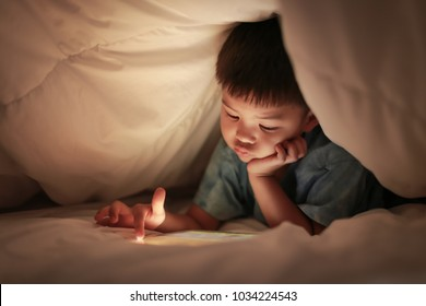Little boy kid using tablet play internet online game, finger hand pointing at touchscreen, while lying under white duvet in the bedroom at night, bright screen light reflex on his face.