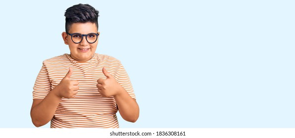 Little boy kid wearing casual clothes and glasses success sign doing positive gesture with hand, thumbs up smiling and happy. cheerful expression and winner gesture.